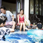 Family playing in comfortable water temperature for swimming